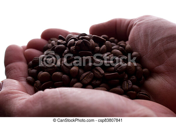 Man's hand a handful of coffee beans - silhouette - csp83807841