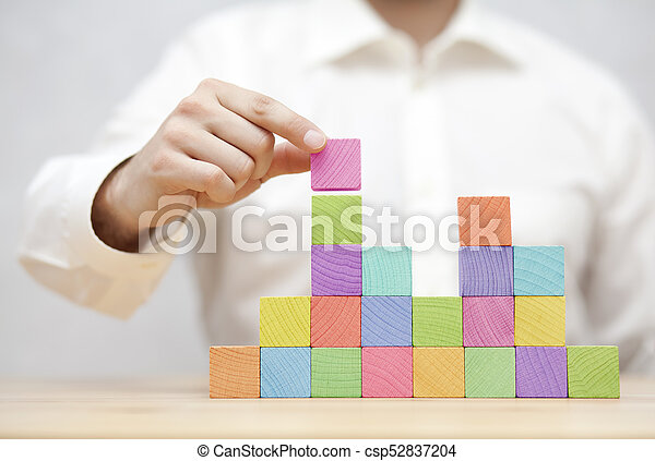 Man's hand stacking colorful wooden blocks. Business development concept - csp52837204