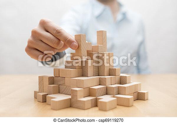 Man's hand stacking wooden blocks. Business development concept - csp69119270