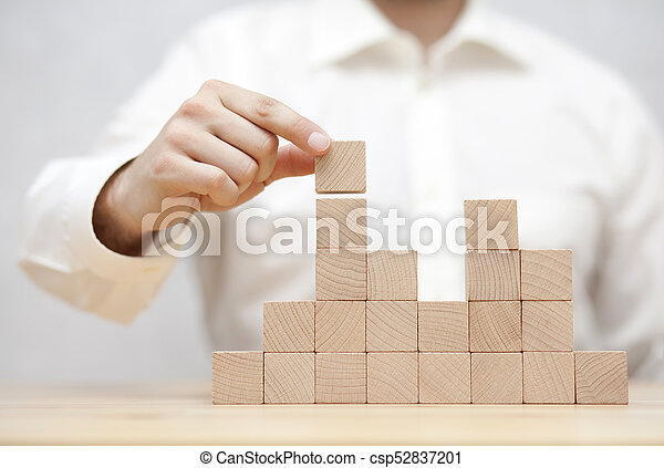 Man's hand stacking wooden blocks. Business development concept - csp52837201