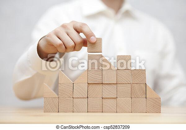Man's hand stacking wooden blocks. Business development concept - csp52837209