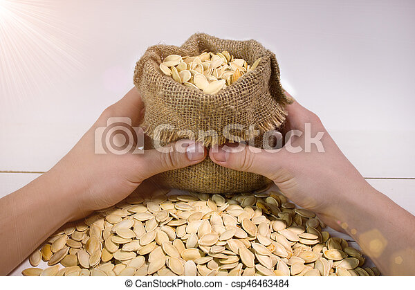 Man's hands holding a sack with a pumpkin seed with flare - csp46463484