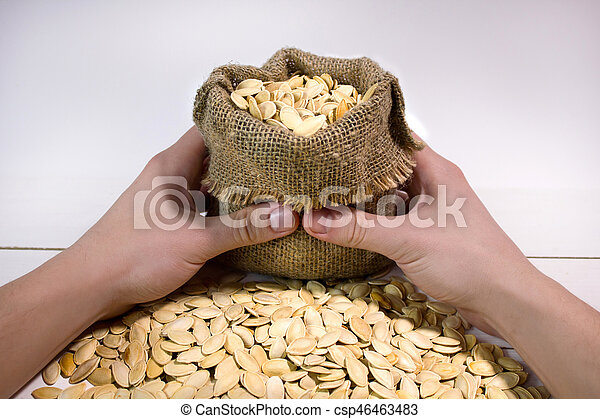 Man's hands holding a sack with pumpkin seed - csp46463483