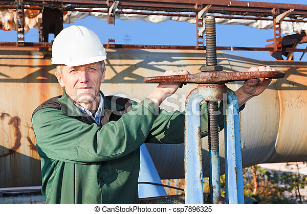 Manual worker turning big valve in industrial plant - csp7896325