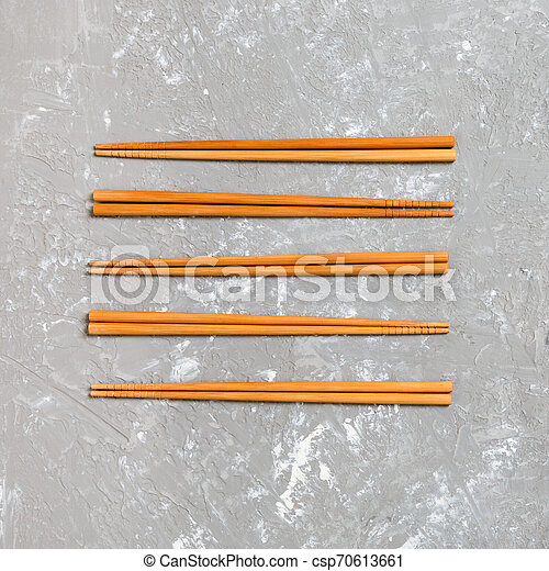 Many bamboo chopsticks on black cement stone background, top view with copy space. a lot of sushi sticks in the form of an ornament - csp70613661
