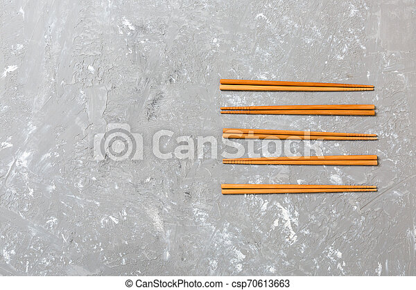 Many bamboo chopsticks on black cement stone background, top view with copy space. a lot of sushi sticks in the form of an ornament - csp70613663
