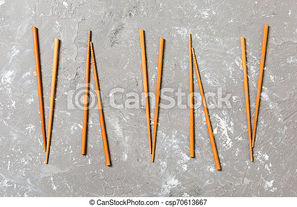Many bamboo chopsticks on black cement stone background, top view with copy space. a lot of sushi sticks in the form of an ornament - csp70613667