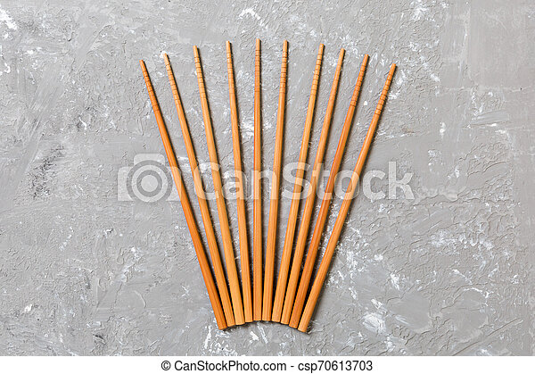 Many bamboo chopsticks on black cement stone background, top view with copy space. a lot of sushi sticks in the form of an ornament - csp70613703