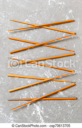 Many bamboo chopsticks on black cement stone background, top view with copy space. a lot of sushi sticks in the form of an ornament - csp70613705