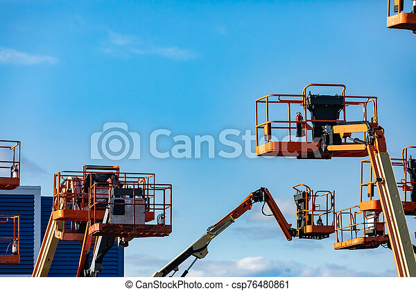 Many cherry pickers against a blue sky - csp76480861