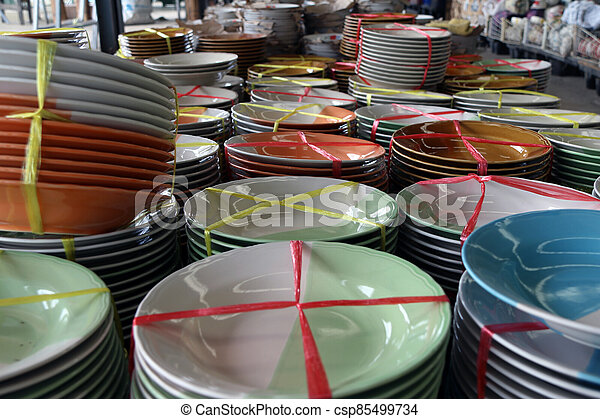 Many dish tied together with straw rope at the dish shop in the market. - csp85499734