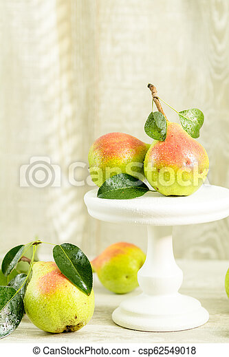 Many juicy beautiful amazing nice pears on light wooden background - csp62549018