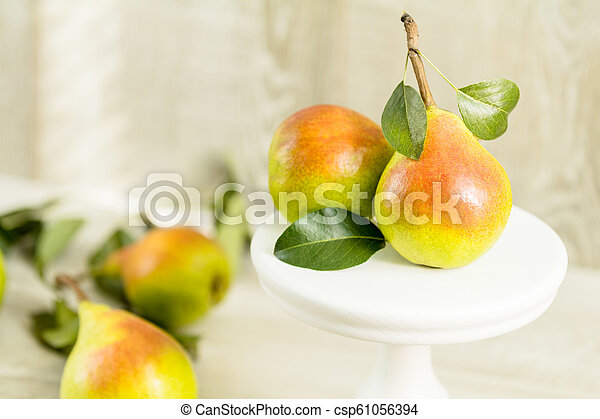 Many juicy beautiful amazing nice pears on light wooden background - csp61056394