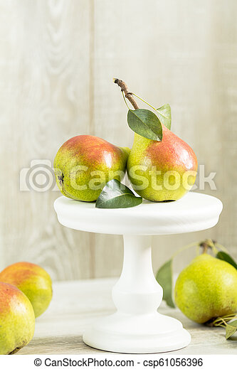 Many juicy beautiful amazing nice pears on light wooden background - csp61056396