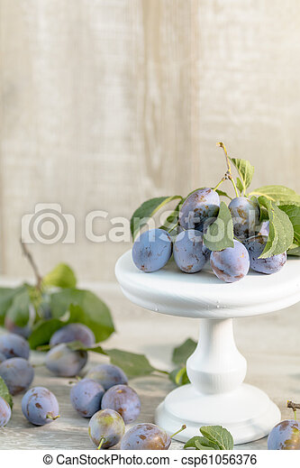 Many juicy beautiful amazing nice plums on light wooden background. - csp61056376