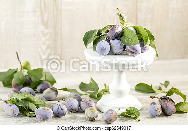 Many juicy beautiful amazing nice plums on light wooden background - csp62549017