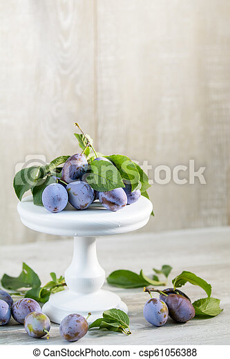 Many juicy beautiful amazing nice plums on light wooden background. Beautiful food art background - csp61056388