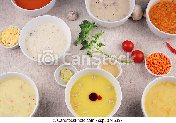 Many plates with different soups on the table - csp58745397