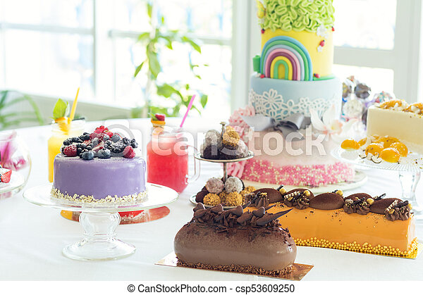 Many sweet pastries on white table with fresh summer berries. Festive table settings. Light background. Shallow depth of field - csp53609250