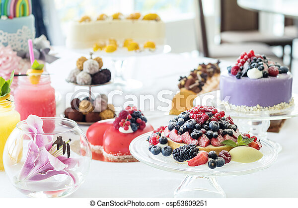 Many sweet pastries on white table with fresh summer berries. Festive table settings. Light background. Shallow depth of field - csp53609251