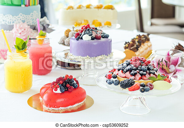 Many sweet pastries on white table with fresh summer berries. Festive table settings. Light background. Shallow depth of field - csp53609252