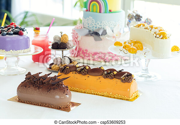 Many sweet pastries on white table with fresh summer berries. Festive table settings. Light background. Shallow depth of field - csp53609253