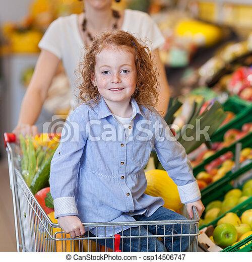 Una chica mostrando manzana con madre en el fondo de la tienda - csp14506747