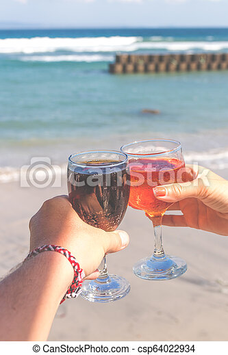 Dos manos sosteniendo vasos con vino en fondo marino. Mujeres y hombres con copas de vino. - csp64022934