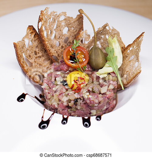Marbled beef tartare on a white plate - csp68687571