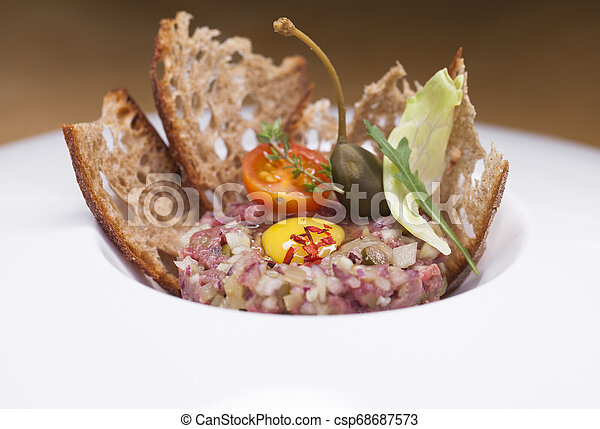 Marbled beef tartare on a white plate - csp68687573