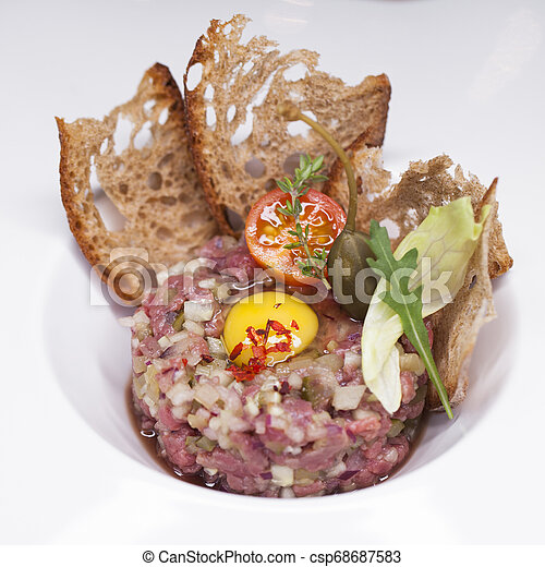 Marbled beef tartare on a white plate - csp68687583