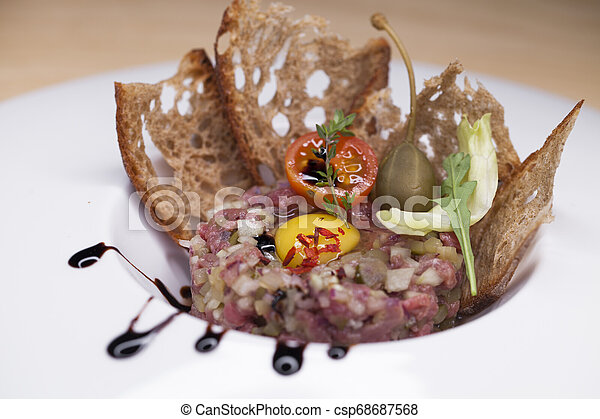 Marbled beef tartare on a white plate - csp68687568