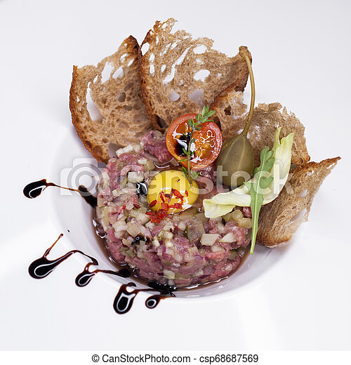 Marbled beef tartare on a white plate - csp68687569