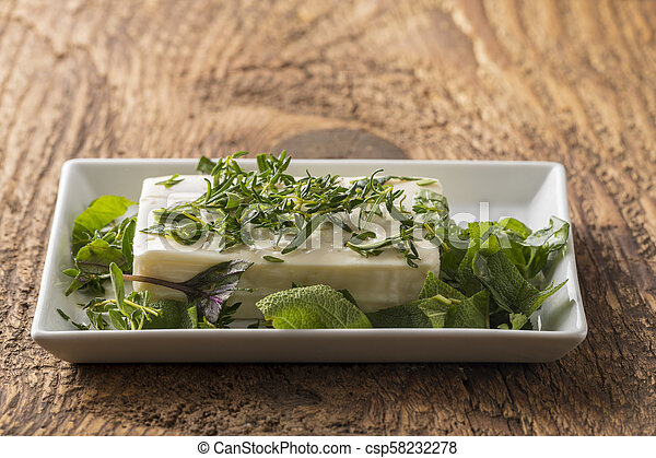 marinating a block of feta cheese with herbs - csp58232278
