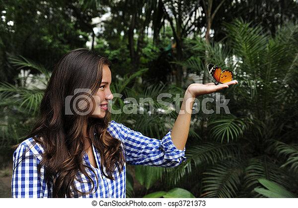 Mariposa sentada en la mano de una joven en el bosque - csp3721373