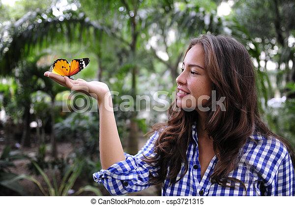 Mariposa sentada en la mano de una joven en el bosque - csp3721315