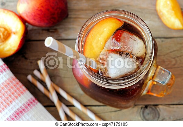Mason Jar Glass Of Homemade Peach Iced Tea On A Rustic Wooden Background Downward View