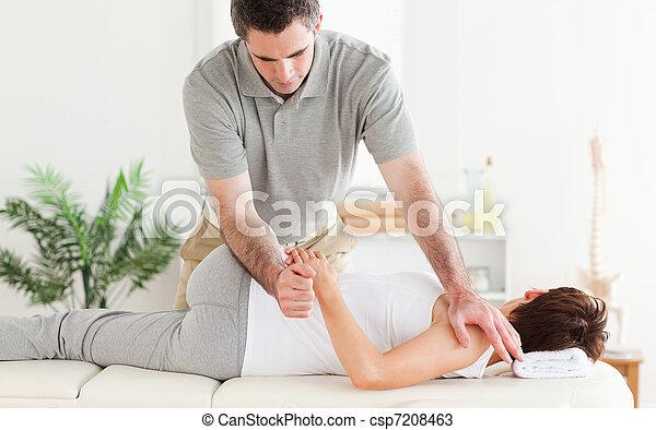 Masseur stretching woman's arm - csp7208463