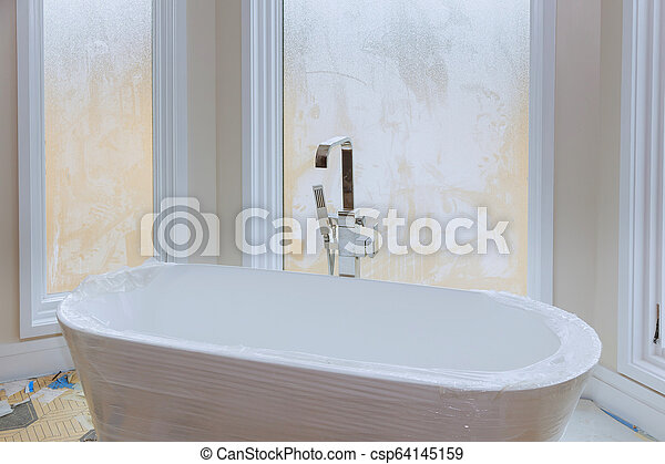 Master bath in new construction home with white tub - csp64145159