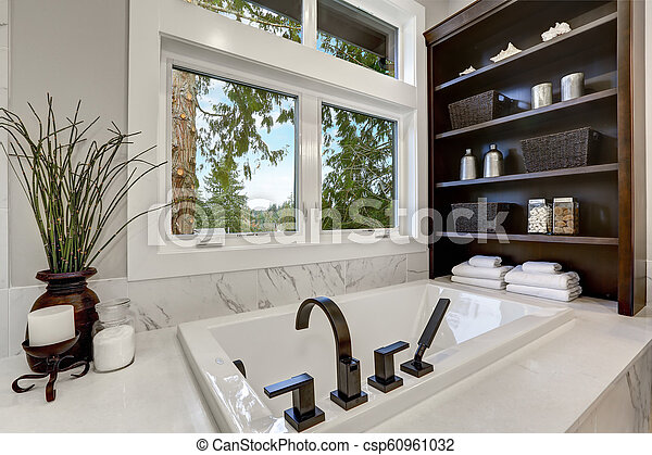 . Master modern bathroom interior in luxury home with dark hardwood cabinets   white tub and glass door shower