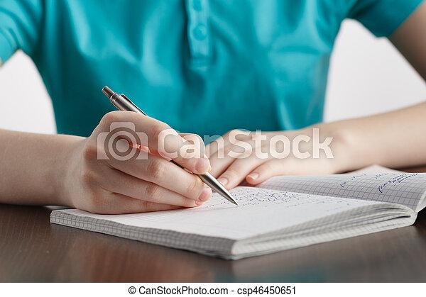 Das Mädchen schreibt in einem Notizbuch mathematische Formeln - csp46450651