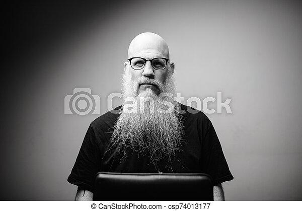 Mature bald man with long gray beard wearing eyeglasses in black and white - csp74013177