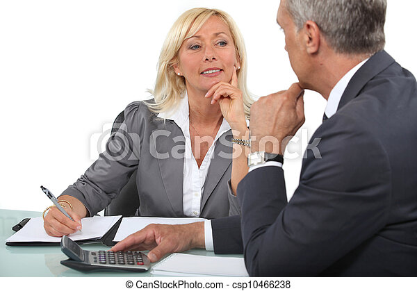 Mature business couple at a desk with a calculator - csp10466238