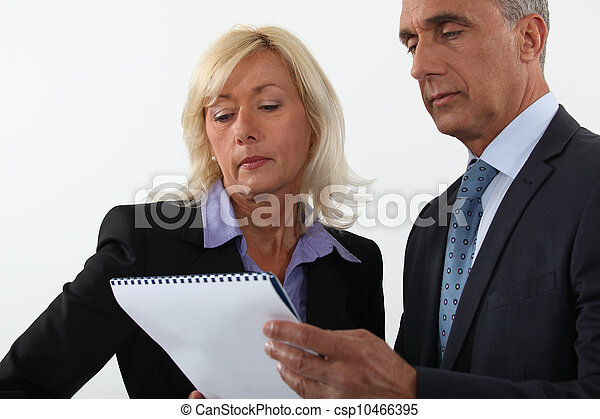 Mature business couple looking at a document - csp10466395