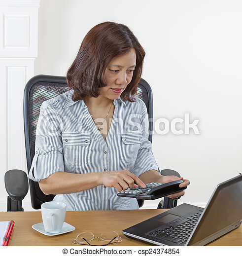 Mature business woman checking numbers with calculator - csp24374854