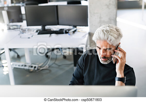 Mature businessman in the office making a phone call. - csp50871803