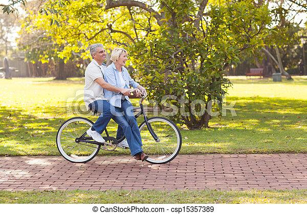 mature couple enjoying bicycle ride - csp15357389