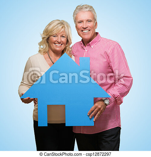 Mature Couple Holding Model Of A House - csp12872297