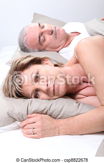 Mature couple laid in bed - csp8822678
