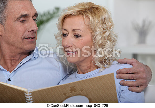 Mature couple looking at a photo album - csp10431729